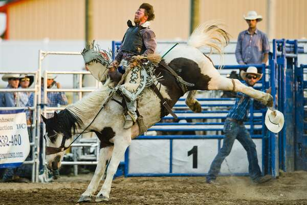 John Miller participates in saddle bronc riding during the Super Kicker Rodeo on Monday, Aug. 13, 2018 at the Midland County Fairgrounds. (Katy Kildee/kkildee@mdn.net)