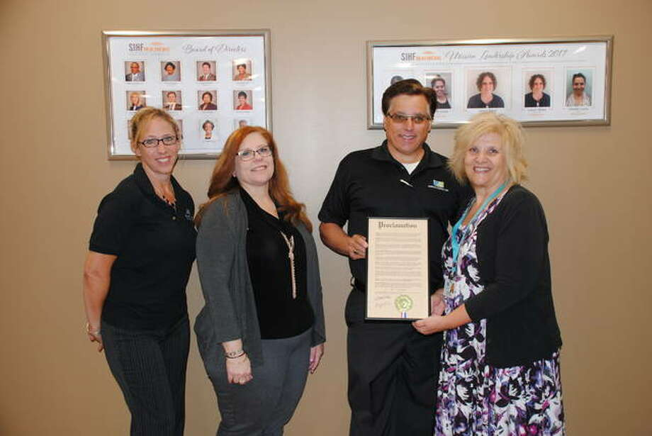 SIHF Healthcare health center managers Carey Runde, Shelley Sumner, and Cathy Sabolo accept a proclamation from Alton Mayor Brant Walker recognizing National Health Center Week. Photo:       For The Telegraph