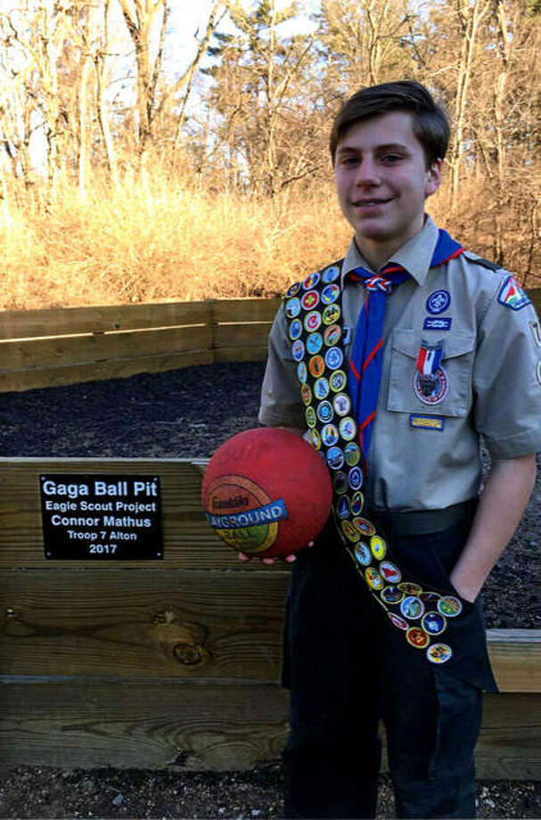 Boy Scout Connor Mathus of Troop 7 holds a gaga ball in front of the ball pit he built for students of St. Ambrose Catholic School in Godfrey. He built the pit as one of his final steps in his quest to achieve Eagle Scout status. Photo:       For The Telegraph