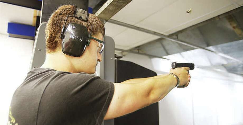 An employee of Piasa Armory fires a handgun in the business's firing range last year. The armory is holding an open house event Saturday. Photo:       John Badman | The Telegraph