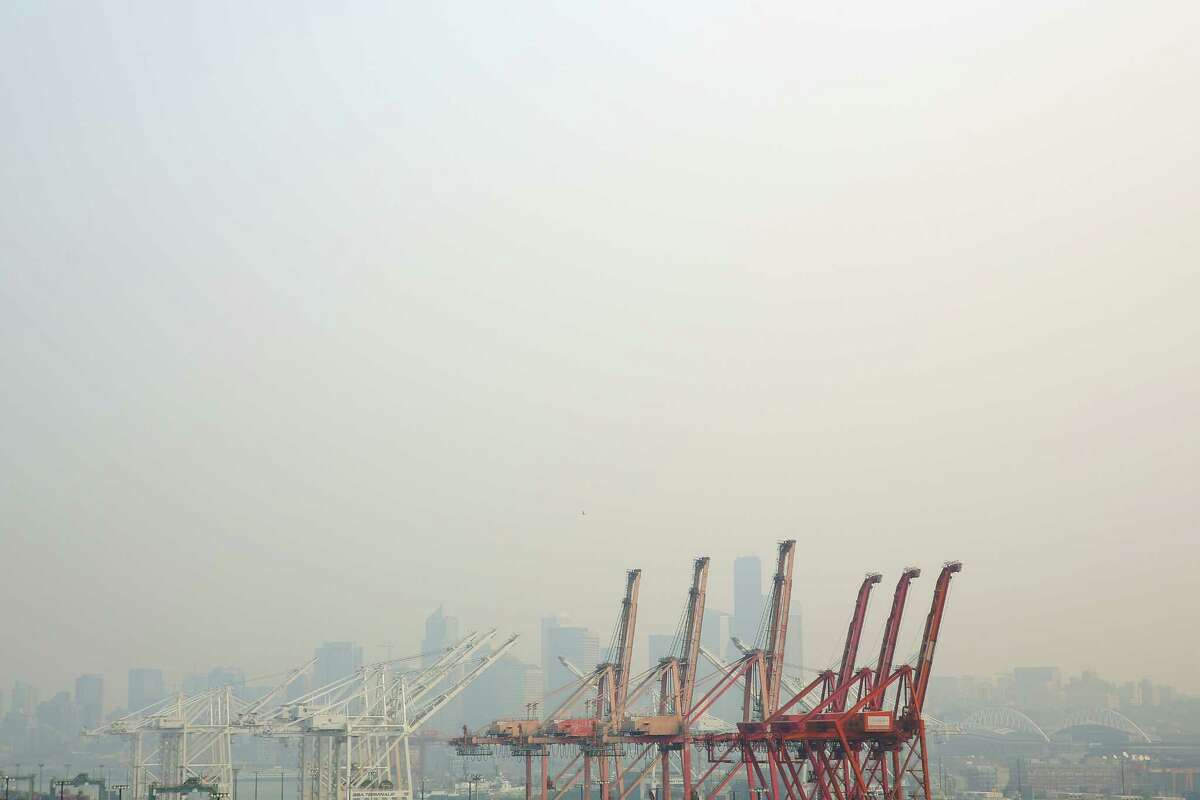 Wildfire smoke causes a thick haze over the shipyards and Seattle skyline, Tuesday, Aug. 14, 2018.