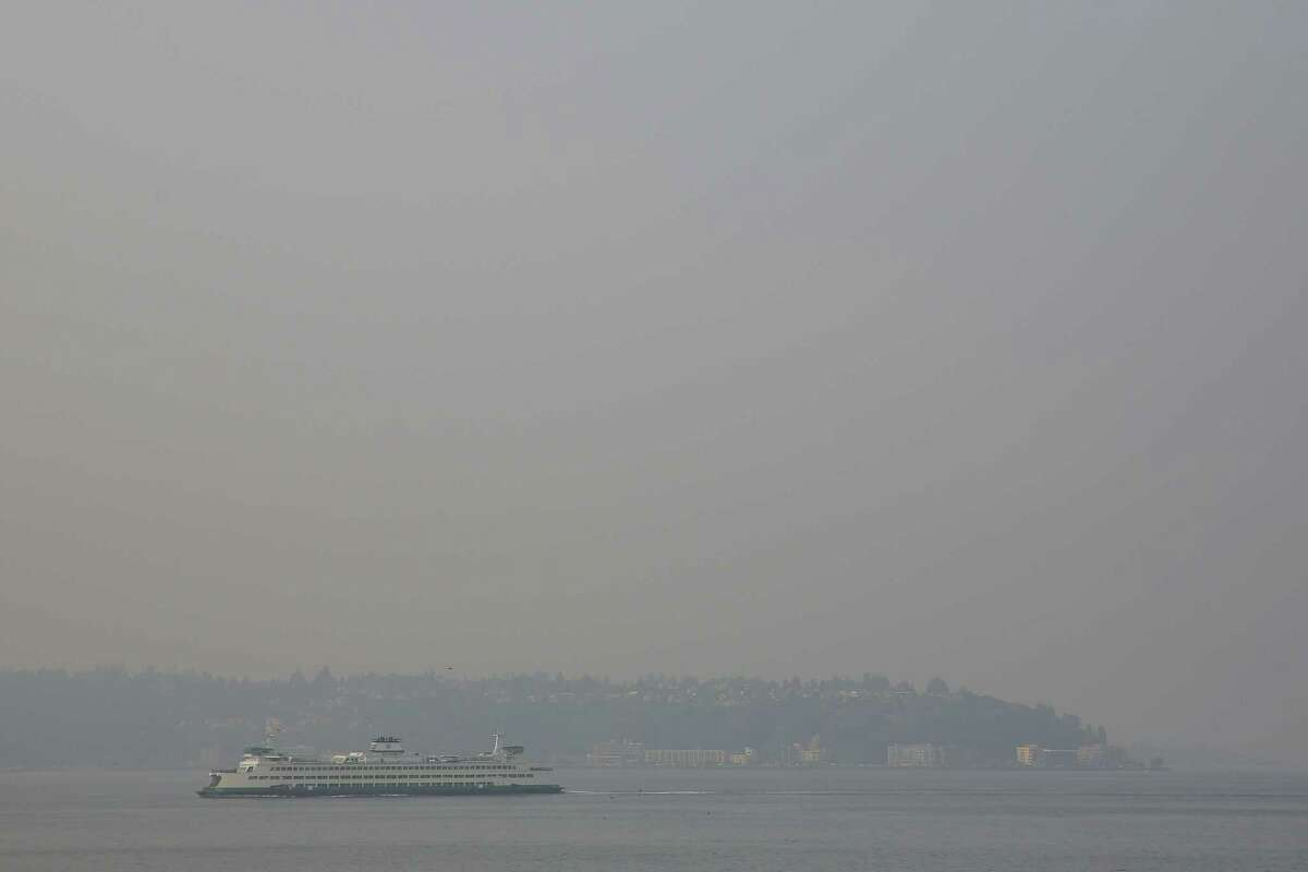 Alki Beach is barely visible from Belltown as smoke causes a thick haze over Seattle, Tuesday, Aug. 14, 2018.
