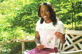 "SIUE senior Corinthia Jordan holds her self-published book of poetry entitled ""Bloom."""