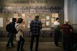 People look at historical publications from the LGBTQ community at the GLBT History Museum in San Francisco, Calif. on Monday, August 13, 2018. The exhibit uses archival materials and artifacts to share historical events of the GLBT community in San Francisco.
