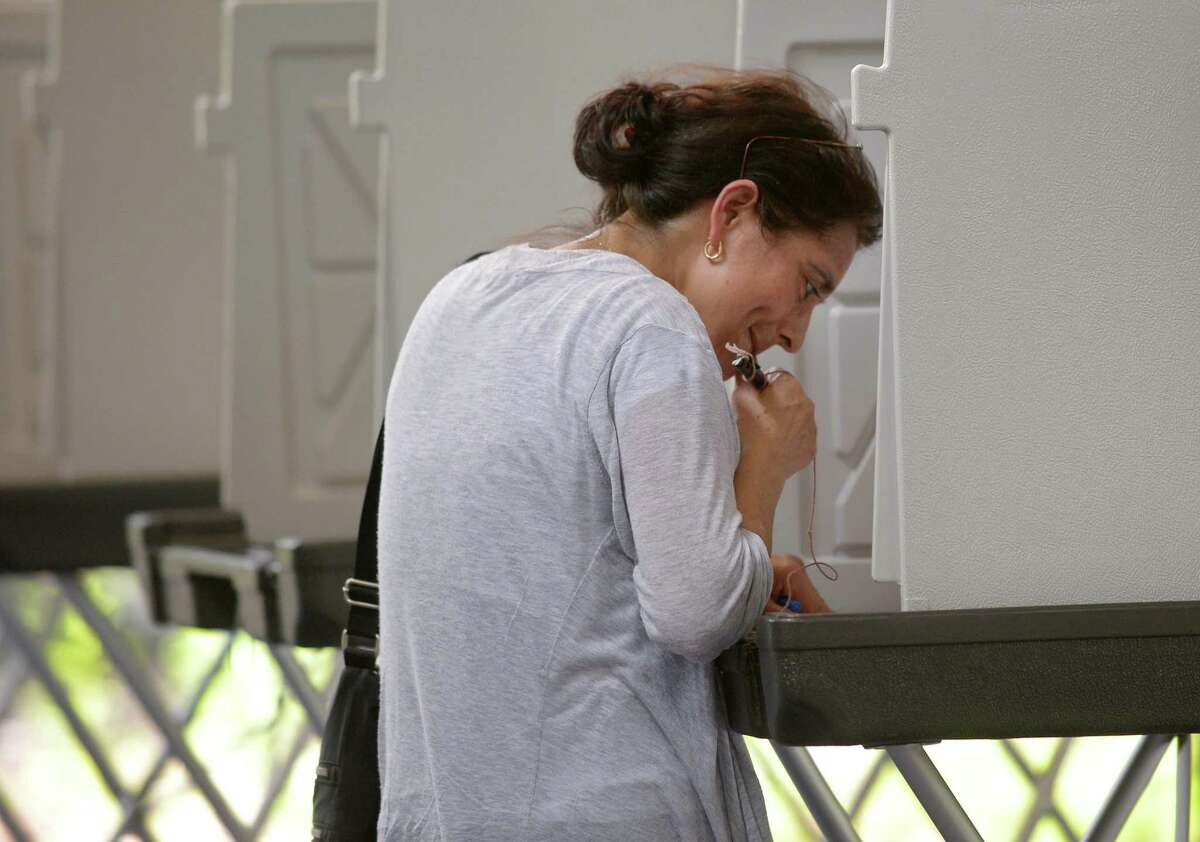 Voters including Maria Landaverde cast their ballots in the primary at the Clune Center Tuesday, August 14, 2018, at Wilton High School in Wilton, Conn.