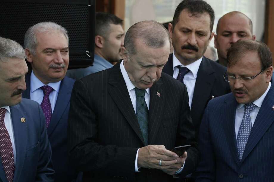In this Friday, May 4, 2018 file photo, Turkey's President Recep Tayyip Erdogan, center, looks at his phone during a ceremony in Istanbul. Erdogan said Tuesday, Aug. 18, 2018, that his country will boycott U.S.-made electronic goods amid a diplomatic spat that has helped trigger a Turkish currency crisis. Showing no signs of backing down in the standoff, Erdogan suggested that Turkey would stop procuring U.S.-made Iphones and buy Korean Samsung or Turkish-made Vestel instead. Photo: Lefteris Pitarakis /Associated Press / Copyright 2018 The Associated Press. All rights reserved