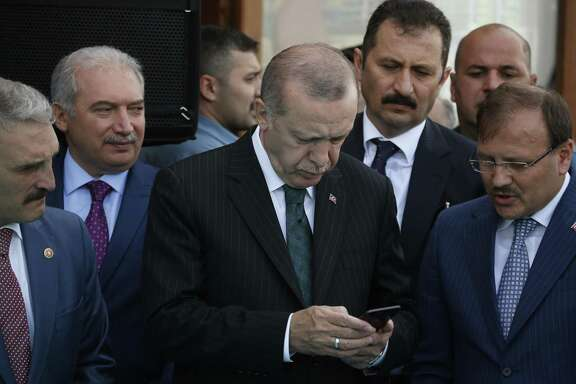 In this Friday, May 4, 2018 file photo, Turkey's President Recep Tayyip Erdogan, center, looks at his phone during a ceremony in Istanbul. Erdogan said Tuesday, Aug. 18, 2018, that his country will boycott U.S.-made electronic goods amid a diplomatic spat that has helped trigger a Turkish currency crisis. Showing no signs of backing down in the standoff, Erdogan suggested that Turkey would stop procuring U.S.-made Iphones and buy Korean Samsung or Turkish-made Vestel instead.
