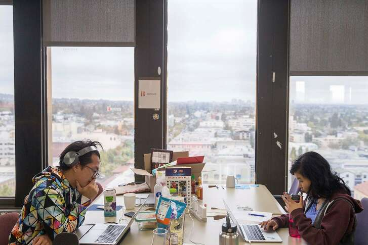 Two members of the startup Bungee work at their desks inside UC Berkeley's SkyDeck startup incubator in Berkeley, Calif. Tuesday, Aug. 14, 2018.