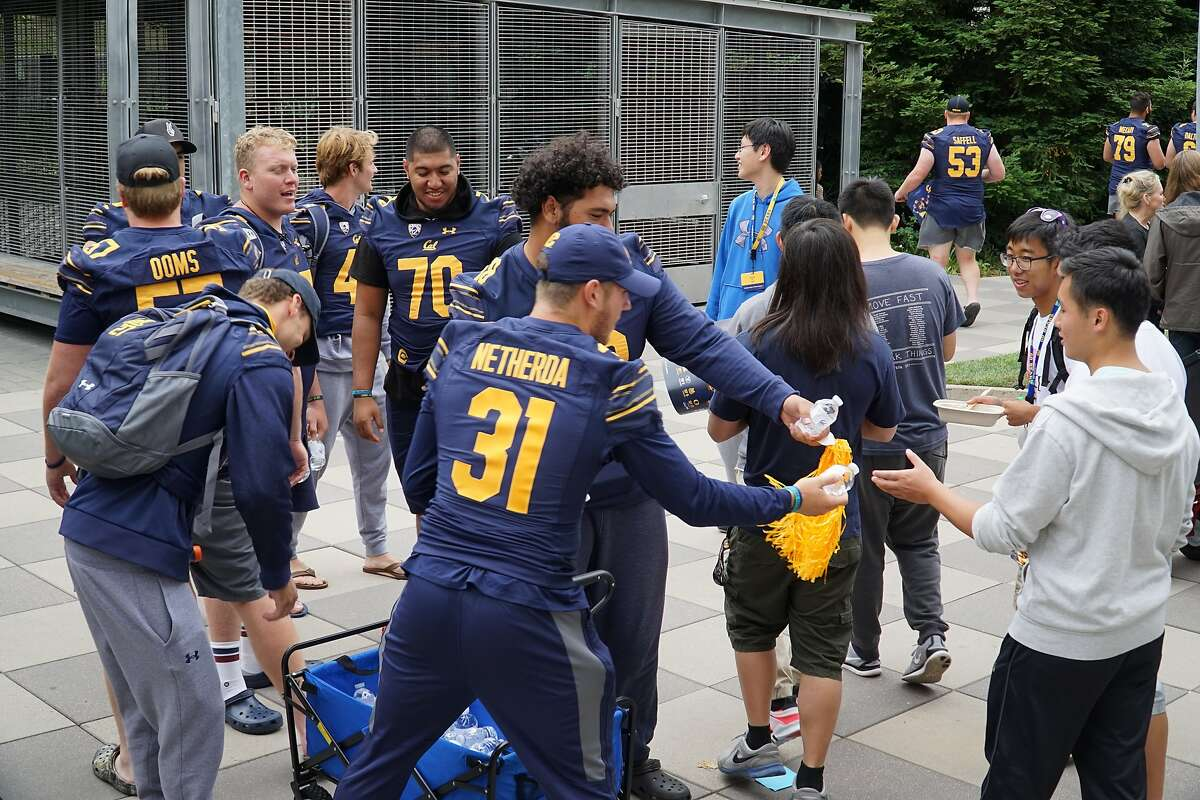 Cal junior running back Alex Netherda passes out water to students moving into dorms on Tuesday in Berkeley.