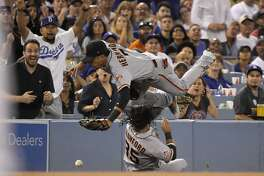 San Francisco Giants left fielder Gorkys Hernandez, top, collides with shortstop Brandon Crawford as they try to field a ball hit for an RBI-double by Los Angeles Dodgers' Clayton Kershaw during the fourth inning of a baseball game, Monday, Aug. 13, 2018, in Los Angeles. Kershaw was thrown out at third on the play. (AP Photo/Mark J. Terrill)