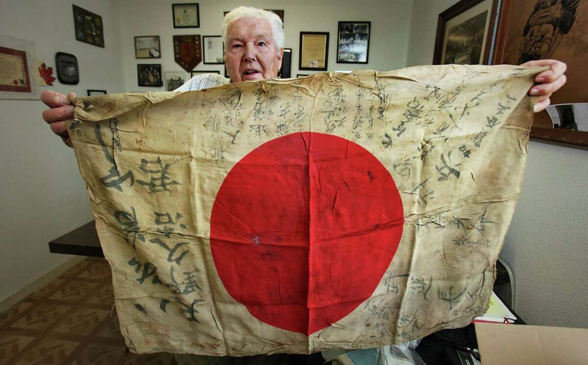 """Retired Army Capt. Clarence Sprouse holds up a silk Japan flag explaining how the flags are presented to soldiers joining the Japan military forces and signed by family and loved ones. The flag iwas carried, sometimes worn under the uniform. Sprouse collected a number of these, stating, """"you might be able to see the bullet hole where he was shot"""". Sprouse recalls his days fighting in WWII, Korea, Vietnam, and as head trainer for the Cuban Bay of Pigs. He has been called """"The Perfect Soldier"""" by some of his superiors. Friday, Oct. 14, 2011. Photo Bob Owen/rowen@express-news.net"""