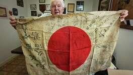 "Retired Army Capt. Clarence Sprouse holds up a silk Japan flag explaining how the flags are presented to soldiers joining the Japan military forces and signed by family and loved ones. The flag iwas carried, sometimes worn under the uniform. Sprouse collected a number of these, stating, ""you might be able to see the bullet hole where he was shot"". Sprouse recalls his days fighting in WWII, Korea, Vietnam, and as head trainer for the Cuban Bay of Pigs. He has been called ""The Perfect Soldier"" by some of his superiors. Friday, Oct. 14, 2011. Photo Bob Owen/rowen@express-news.net"
