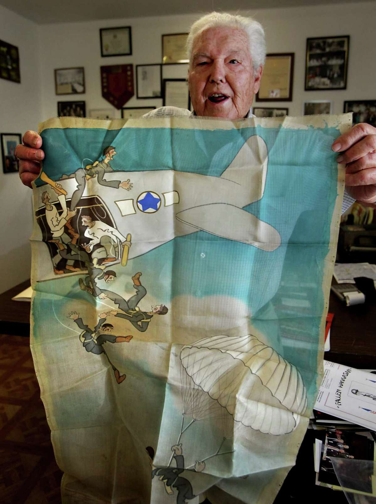 """Metro adv - Retired Army Capt. Clarence Sprouse, holding up a Japanese military propaganda poster printed on silk, recalls his days fighting in WWII, Korea, Vietnam, and as trainer for the Cuban Bay of Pigs. The poster insinuates the U.S. forced soldiers to serve in the army. Sprouse has been called """"The Perfect Soldier"""" by some of his superiors. Friday, Oct. 14, 2011. Photo Bob Owen/rowen@express-news.net"""