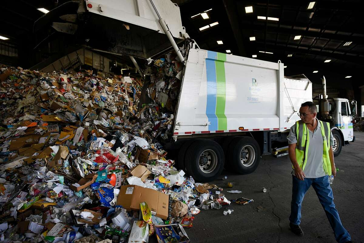 Employee Owner Tom Phillips watches as a truck drops recycling onto a pile at Recology Vallejo in Vallejo, Calif., on Tuesday, August 14th, 2018.