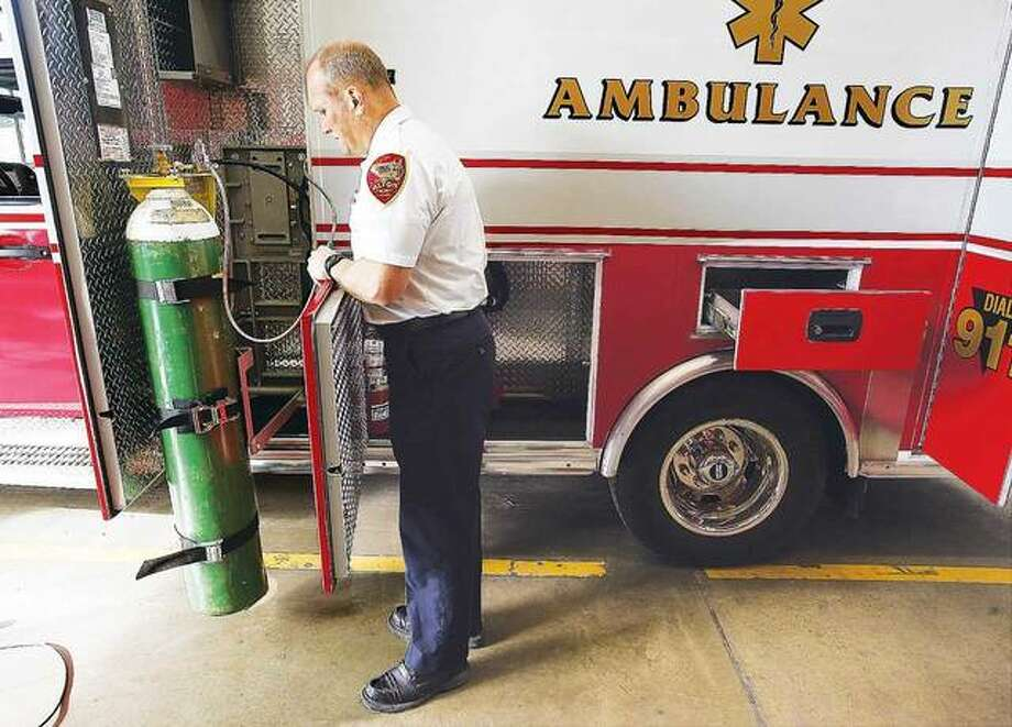In this January 2017 photo, Alton Fire Chief Bernie Sebold uses the automated lift, which takes the effort out of changing the heavy tank of breathing oxygen used by patients. AFD recently began responding to calls for ambulance service to East Alton when Alton Memorial Ambulance Service has no truck available, as a secondary option. Photo:       John Badman | The Telegraph
