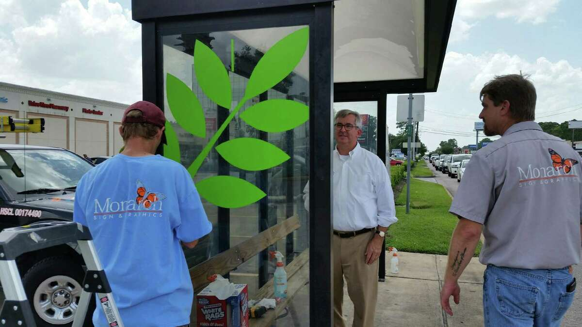 The Houston Northwest Chamber's strategic plan intends to address issues impacting the community, such as improvement efforts along FM 1960. Shown here: Bobby Lieb, with the Houston Northwest Chamber of Commerce (center), looks on as Tiger Berry (left) and Mike Shaffer of Monarch Signs & Graphics apply a logo to a bus shelter near 5603 FM 1960 in north Houston on August 14, 2018.