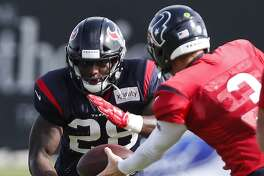 Houston Texans running back Alfred Blue (28) takes a handoff from quarterback Brandon Weeden (3) during training camp at the Methodist Training Center on Tuesday, Aug. 14, 2018, in Houston.