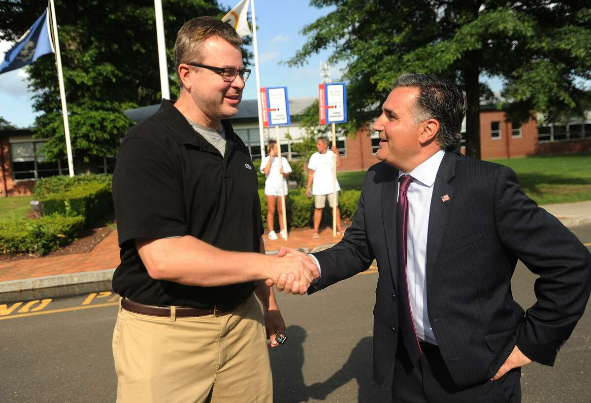 Republican candidate for the district 14 state senate primary Anthony Giannattasio, right, greets voter Brian McGrew, of Orange, outside the polls at the Orange Community Center in Orange, Conn on Tuesday, August 14, 2018.