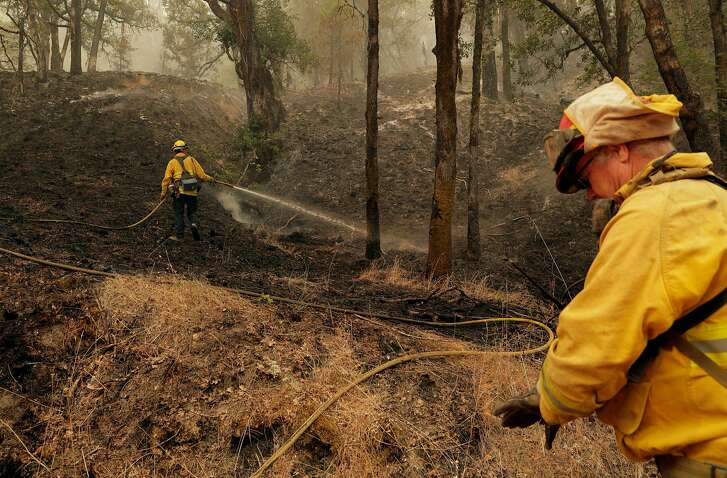 Firefighters tend to hotspots in a back-burned area in the Mendocino National Forest that was burned in the Mendocino Complex Fire east of Ukiah, Calif., on Tuesday, August 14, 2018.