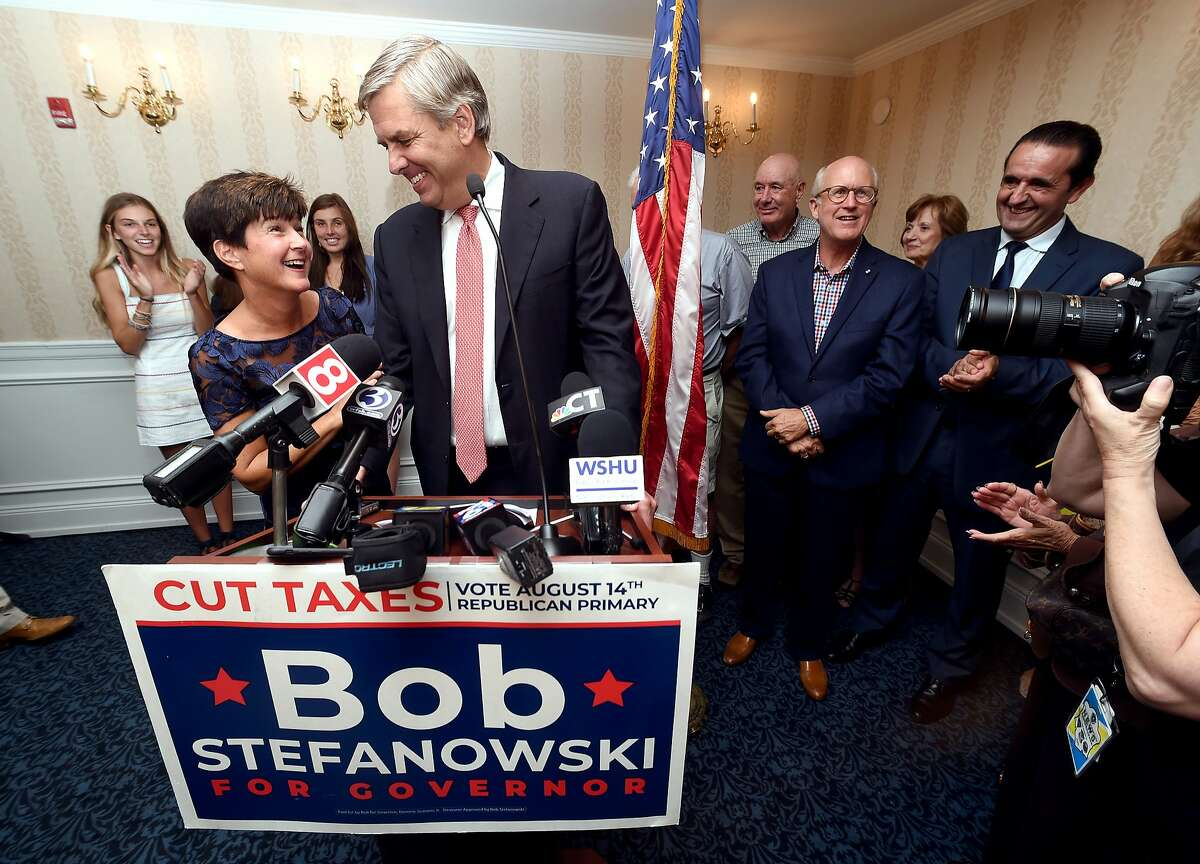 Republican gubernatorial candidate Bob Stefanowski speaks to supporters at the Madison Beach Hotel in Madison flanked by his wife, Amy, on August 14, 2018.