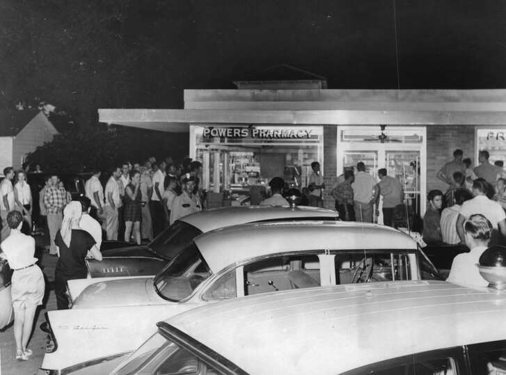 Bystanders flock to Powers Drug Store on North Main on Aug. 15, 1959, where bandit was killed.