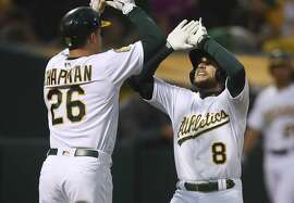Oakland Athletics' Jed Lowrie, right, celebrates with Matt Chapman (26) after hitting a two-run home run off Seattle Mariners' Felix Hernandez in the third inning of a baseball game Tuesday, Aug. 14, 2018, in Oakland, Calif. (AP Photo/Ben Margot)