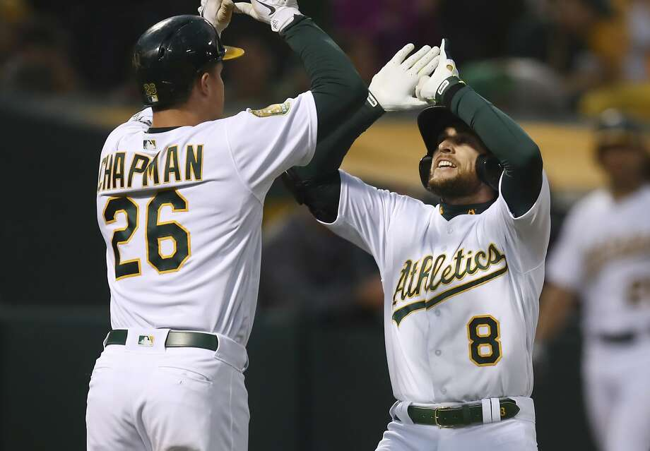 Oakland Athletics' Jed Lowrie, right, celebrates with Matt Chapman (26) after hitting a two-run home run off Seattle Mariners' Felix Hernandez in the third inning of a baseball game Tuesday, Aug. 14, 2018, in Oakland, Calif. (AP Photo/Ben Margot) Photo: Ben Margot / Associated Press