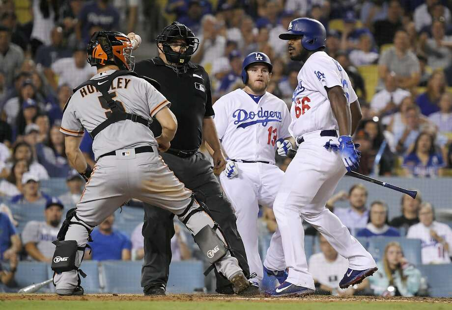 San Francisco Giants catcher Nick Hundley, left, reacts to being shoved by Los Angeles Dodgers' Yasiel Puig, right, as they argue while home plate umpire Eric Cooper, second from left, gets between them and Max Muncy runs in during the seventh inning of a baseball game, Tuesday, Aug. 14, 2018, in Los Angeles. (AP Photo/Mark J. Terrill) Photo: Mark J. Terrill / Associated Press