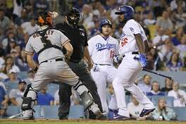 San Francisco Giants catcher Nick Hundley, left, reacts to being shoved by Los Angeles Dodgers' Yasiel Puig, right, as they argue while home plate umpire Eric Cooper, second from left, gets between them and Max Muncy runs in during the seventh inning of a baseball game, Tuesday, Aug. 14, 2018, in Los Angeles. (AP Photo/Mark J. Terrill)