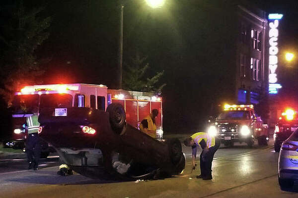 A two crew attends to a vehicle that overturned in a single-vehicle accident at Broadway and Ridge Street early Wednesday morning.