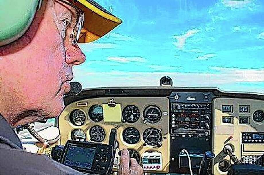 Pilot Neil Fotzler talks to the air traffic controller at Willard Airport during a flight in Savoy. In 2002, the Champaign resident was approached by the Experimental Aviation Association, an organization that promotes recreational flying, asking if he'd be a volunteer pilot for their Young Eagles initiative. Photo:       Vishesh Anand | News-Gazette (AP )