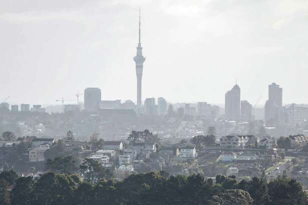 Houses stand in suburban Mount Wellington as the Sky Tower stands in the distance in Auckland, New Zealand, on July 20, 2015.