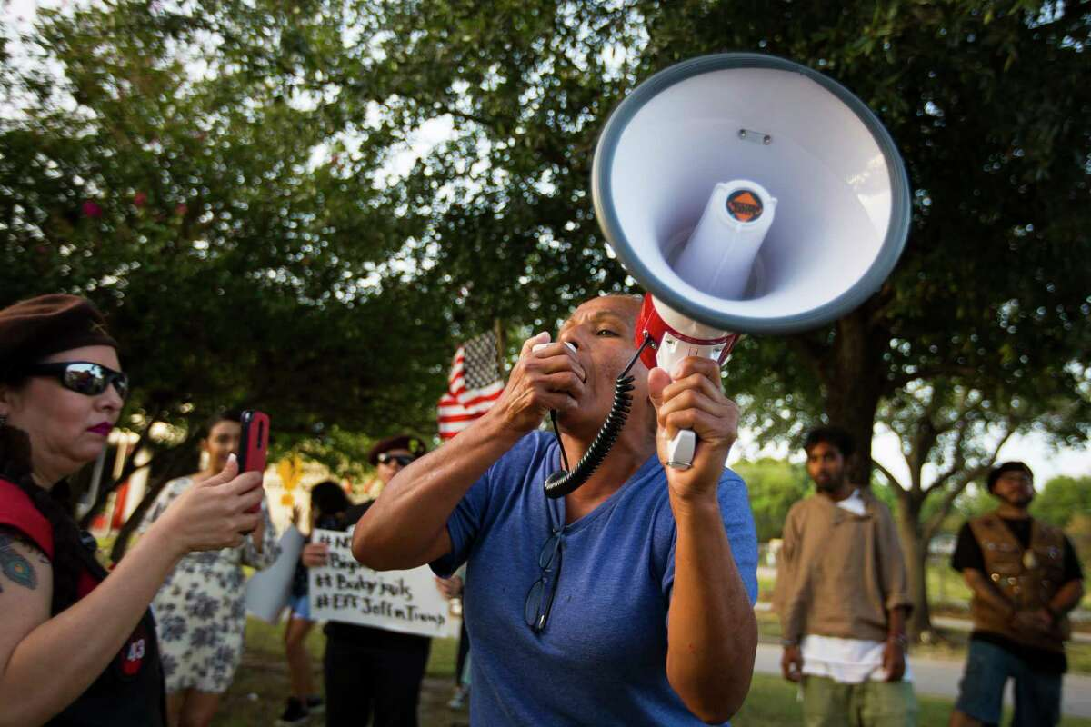 """Janie Torres speaks into a megaphone on the median of Navigation Blvd. in front of El Tiempo, Monday, Aug. 13, 2018 in Houston. Torres was born and raised in the neighborhood and said it was """"unacceptable"""" that the restaurant celebrated Attorney General Jeff Sessions' visit last week."""