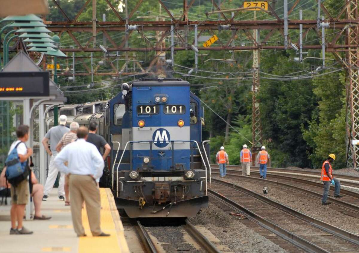 Commuters on the south platform of the Central Greenwich Train Station watch as Metro-North Railroad workers appear to be checking the tracks of the west-bound rails into New York City as a train on the east-bound side sits idle early Saturday evening, July 10, 2010.