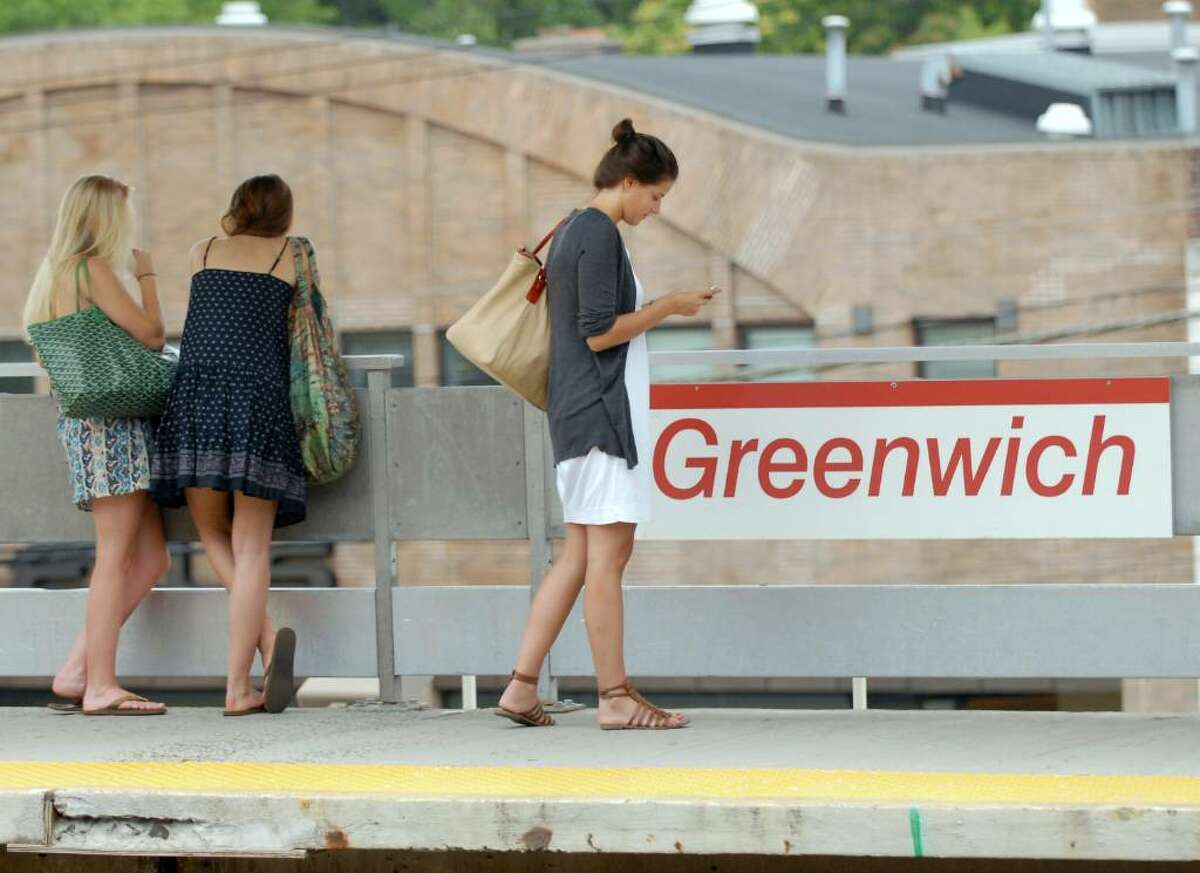 Lizzie McGirr of Greenwich, right, texts a friend while waiting for her train into New York City at the Central Greenwich Train Station, early Saturday evening, July 10, 2010. Trains were delayed in both directions for over two hours while Metro-North workers attempted to fix damaged wires just west of the Central Greenwich Station. McGirr gave up and went home instead.