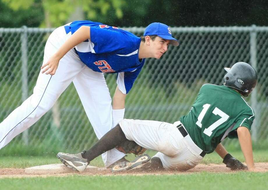 Chris DiRusso successfully steals Stamford third baseman looks for the official call from the umpire. Greenwich plays Stamford in the U14 Babe Ruth League Playoffs on Saturday, July 10 at Greenwich High School. Photo: David E. Johnston / Greenwich Time Freelance