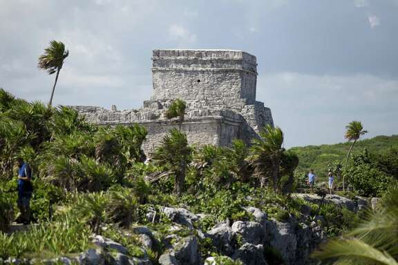 In this Aug. 5, 2018 photo, tourists vist the archeological site of Tulum on Mexico's Yucatan Peninsula. Almost seven million international tourists visit this stretch of coast every year; many of whom arrive at the Cancun airport and are bused or drive down the coast.