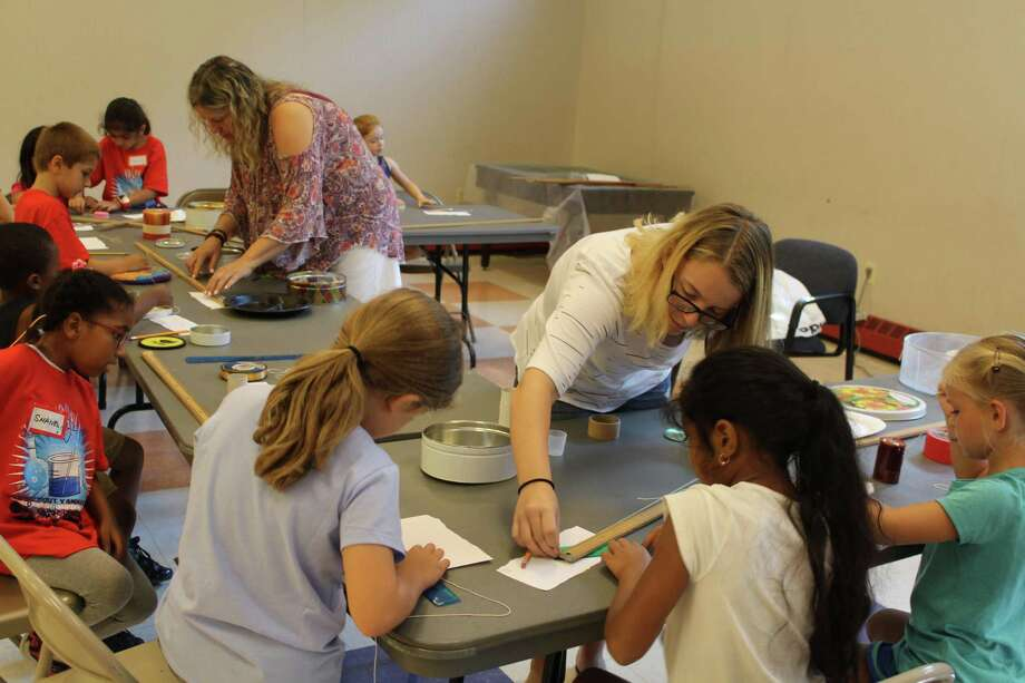 Julia Pfrommer helping Tisha Saffa teach students at the STEM camp. Taken Aug. 14. Photo: /provided By Lynandro Simmons /Hearst Media