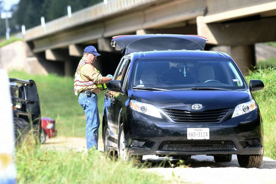Hardin County officials investigate the discovery of a woman's body under the Highway 327 bridge at Village Creek Wednesday morning. The body was found around 8:45 and officials said she had been camping with her family when she went missing.     Photo taken Wednesday, 8/15/18 Photo: Guiseppe Barranco/The Enterprise