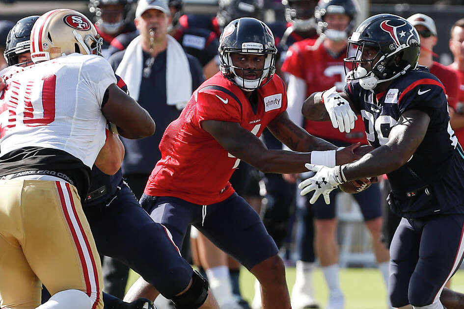 Houston Texans quarterback Deshaun Watson (4) hands the ball off to running back Lamar Miller (26) as San Francisco 49ers defensive tackle Earl Mitchell (90) defends during a joint practice betwen the Texans and 49ers at the Methodist Training Center on Wednesday, Aug. 15, 2018, in Houston.