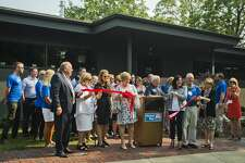 Ann Fillmore, executive director of United Way of Midland County, cuts a ribbon in front of the organization's new building on Tuesday, Aug. 14, 2018 at 115 Jerome Street. (Katy Kildee/kkildee@mdn.net)
