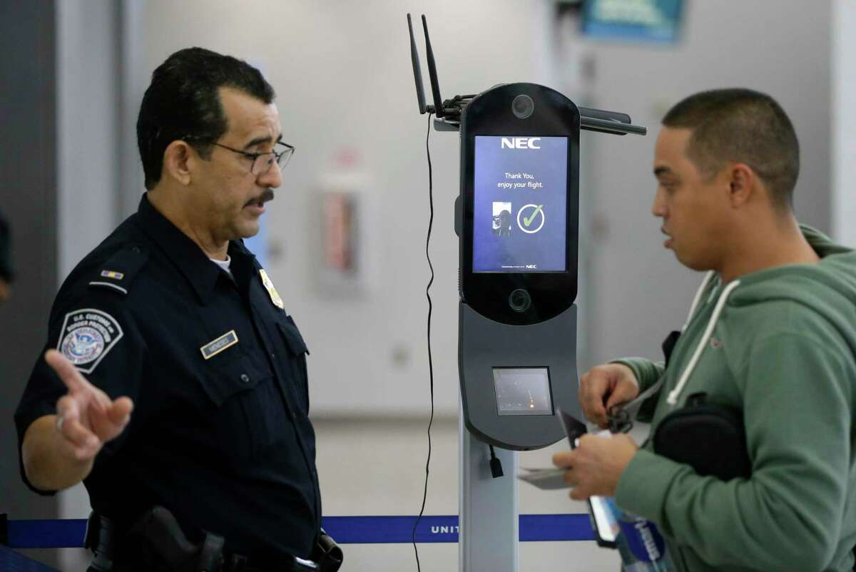 U. S. Custom and Border Protection officer M. Meneses, left, directs a passenger to move forward at gate after he used a biometric exit camera on the passenger boarding an outbound United flight to Japan in Terminal E at George Bush Intercontinental in Houston Friday, Aug. 10, 2018, in Houston.