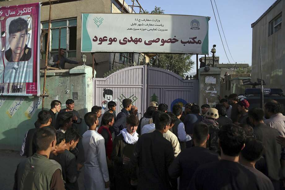 People gather at the site of a suicide bombing that targeted a university preparatory course in Kabul. Photo: Rahmat Gul / Associated Press