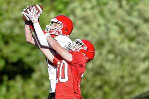 New Canaan's Wyatt Wilson (80) and Will Rechtermann (20) fight for a pass during the 11th Annual Brian Wilderman Memorial Red and White football game at Dunning Stadium in New Canaan.
