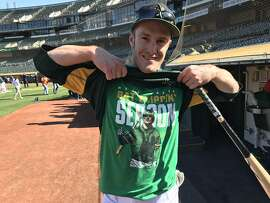 "Mark Canha of the Oakland Athletics shows off his ""Bat-flipping season"" t-shirt before the A's faced the Toronto Blue Jays at  Oakland Coliseum on Monday July 30, 2018."