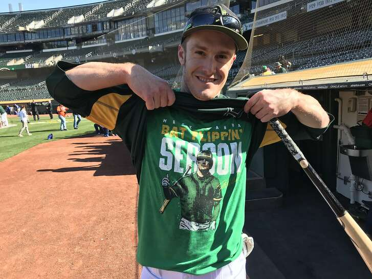 """Mark Canha of the Oakland Athletics shows off his """"Bat-flipping season"""" t-shirt before the A's faced the Toronto Blue Jays at  Oakland Coliseum on Monday July 30, 2018."""