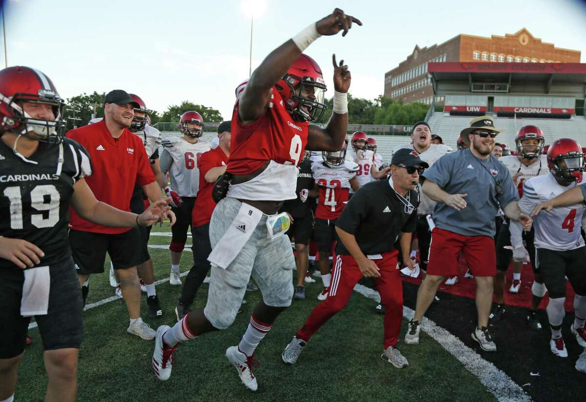"""Head coach Eric Morris and Mar'kel Cooks, left, react during """"Bull in the Ring"""" drill at UIW football practice at Benson Field on Wednesday, Aug. 8, 2018."""
