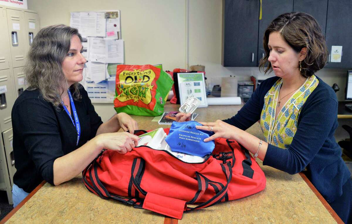 Albany Public Library community services and support specialist Annie Johnson, left, and assistant director Melanie Metger with a Narcan kit for drug overdoses in one of the emergency bags at the library's main branch Wednesday August 15, 2018 in Albany, NY. (John Carl D'Annibale/Times Union)