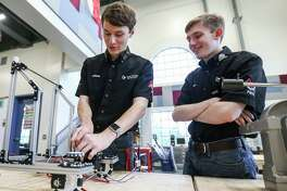Texas Torque team members Jackson Schilling, left, and Conner Palandro, right, work together on a robot Tuesday, Aug. 14, 2018, at College Park High School. Texas Torque, College Park's FIRST Robotics Team, is building a robot to take to the FIRST Global Robotics Competition in Mexico City to replace the robot of the female team from Afghanistan, who lost their robot in transit.