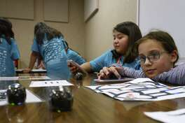 Kendall Cales, right, and Emilia Ybarra demonstrate the use of Ozobots in their study of robotics and programming at a Girlstart STEM Galaxy camp.